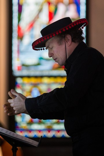 Conductor Ronald Mutchnik wears a traditional Spanish hat while he leads the orchestra in a song. (Nate Pesce/BSMG)