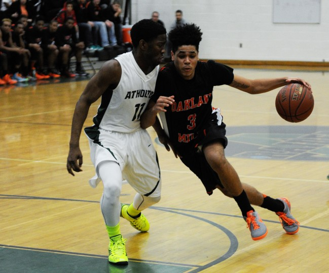 Oakland Mills' Daniel Kiely, right, tries to escape pressure by Atholton's Joelle Martin during a basketball game at Atholton High School in Columbia on Monday, Jan. 13, 2013. (Jon Sham/BSMG)
