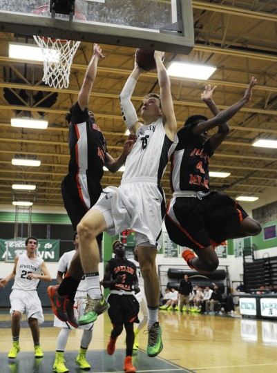 Atholton's Justin Ballmer, center, is flanked by Oakland Mills' Daniel Kiely, left, and Marvin Williams as he goes up to the board during a basketball game at Atholton High School in Columbia on Monday, Jan. 13, 2013. (Jon Sham/BSMG)