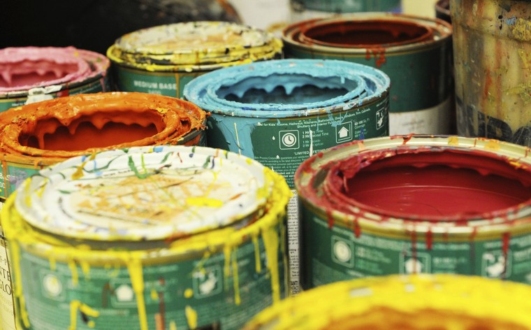 Paint cans are strewn about in a hallway in the Monarch Academy Public Charter School Baltimore as artists work on murals in mid-November. (Jon Sham/BSMG)