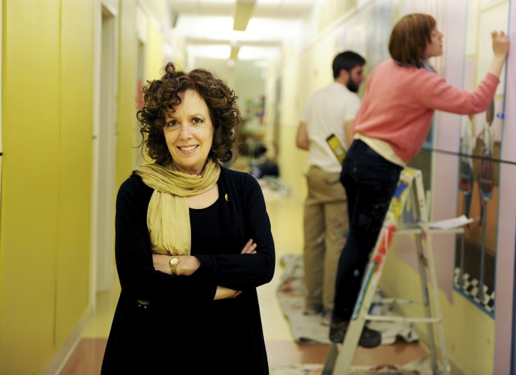 Nancy Scheinman poses for a photo in a hallway at the Monarch Academy in Baltimore, as she and her crew work on murals for the school on Wednesday, Nov. 13, 2013. (Jon Sham/BSMG)