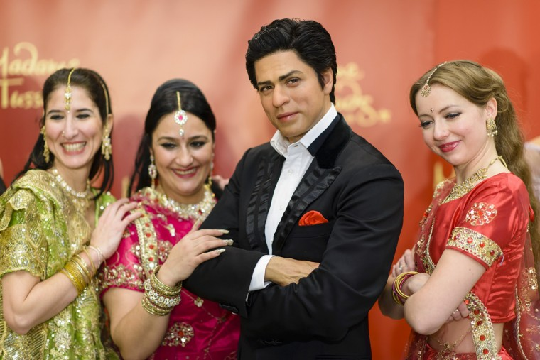 Dancers pose with the wax figure of Shah Rukh Khan during a photocall in the Indian embassy on December 18, 2013 in Berlin, Germany. (Clemens Bilan/Getty Images)