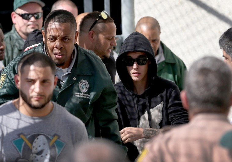 Justin Bieber (R) exits from the Turner Guilford Knight Correctional Center on January 23, 2014 in Miami, Florida. Justin Bieber was charged with drunken driving, resisting arrest and driving without a valid license after Miami Beach police found the pop star street racing Thursday morning. (Joe Raedle/Getty Images)