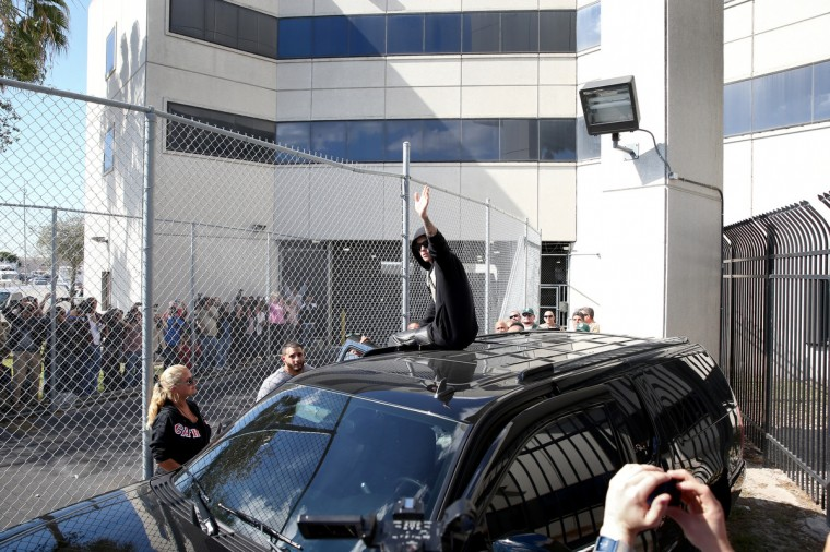Justin Bieber waves after exiting from the Turner Guilford Knight Correctional Center on January 23, 2014 in Miami, Florida. Justin Bieber was charged with drunken driving, resisting arrest and driving without a valid license after Miami Beach police found the pop star street racing Thursday morning. (Joe Raedle/Getty Images)