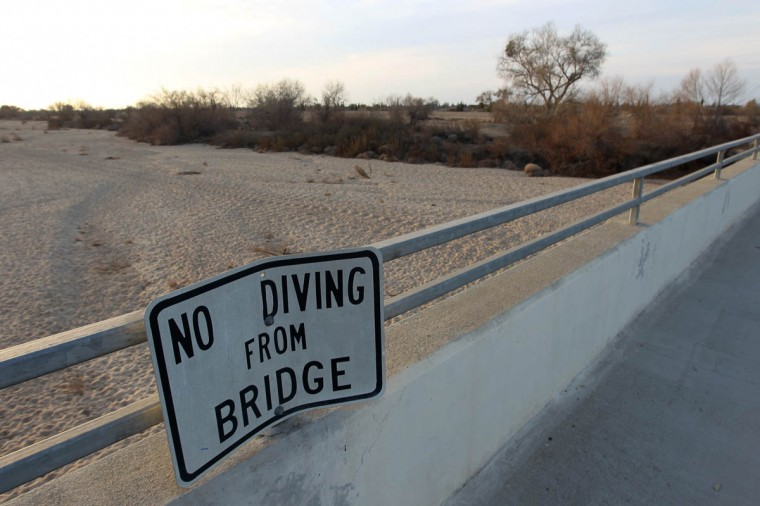 A sign from wetter times warns people not to dive from a bridge over the Kern River, which has been dried up by water diversion projects and little rain, on February 4, 2014 in Bakersfield, California. Now in its third straight year of unprecedented drought, California is experiencing its driest year on record, dating back 119 years. Grasslands that support cattle have dried up, forcing ranchers to feed them expensive supplemental hay to keep them from starving or to sell at least some of their herds, and farmers are struggling with diminishing crop water and what to plant or whether to tear out permanent crops which use water year-round such, as almond trees. About 17 rural communities could run out of drinking water within several weeks and politicians are are pushing to undo laws that protect several endangered species. (David McNew/Getty Images)