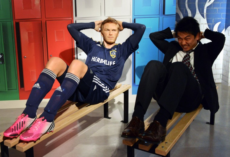 A man mimics the wax figure of football star David Beckham at a press preview of Madame Tussauds museum in Tokyo on March 13, 2013. Tokyo's Madame Tussauds museum will exhibit some 60 wax figures of Japanese and foreign stars when it re-opens on March 15. (Getty Images)