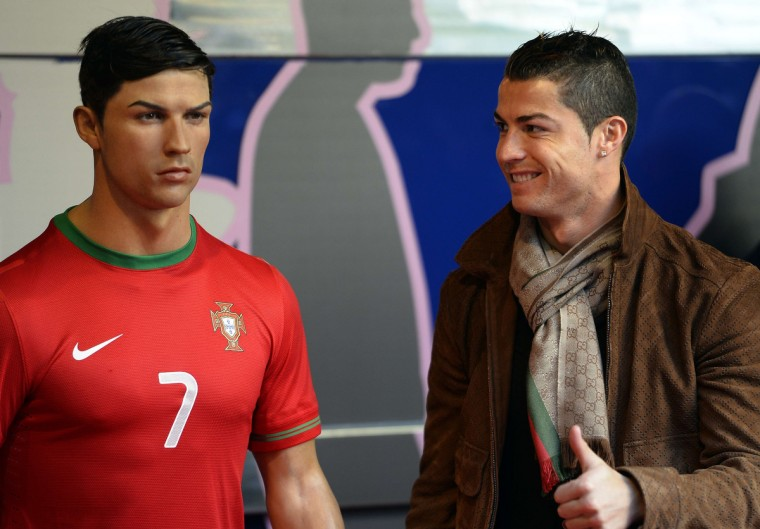 Real Madrid's Portuguese forward Cristiano Ronaldo (R) gives the thumbs up as he poses with his wax figure at the Wax Museum of Madrid. (Gerard Julien/Getty Images)