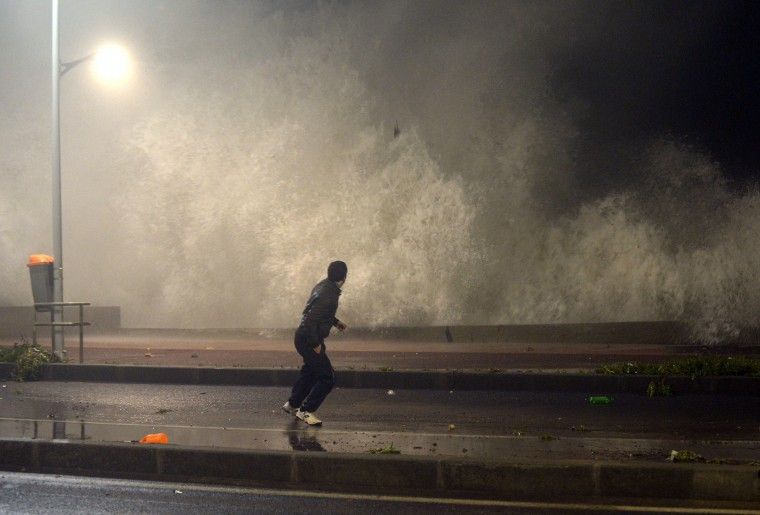 A Moroccan resident runs as a huge wave crashes along the Atlantic costal road in Rabat during high tide on January 7, 2014. The wave was some 8 meters high and threw rocks and debris along the road and sidewalk. (Fadel Senna/AFP/Getty Images)