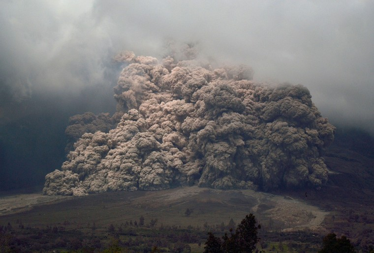 Sinabung mount spews ash to the air during an eruption near from Karo, North Sumatra on January 7, 2014. An Indonesian volcano that has erupted relentlessly for months shot volcanic ash into the air 30 times on January 4, forcing further evacuations with more than 20,000 people now displaced, an official said. (Sutanta Aditya/AFP/Getty Images)