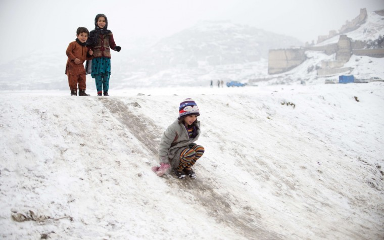 A young Afghan girl slides down a snow-covered hummock during snow-fall in Kabul. As winter sets in across Central Asia, many Afghans struggle to provide adequate food and shelter for their families. (Johannes Eisele/Getty Images)