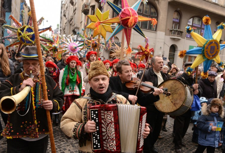 People wear traditional clothes as they sing song and walk during Christmas carnival in western Ukrainian city of Lviv. (Yuriy Dyachyshyn/Getty Images)