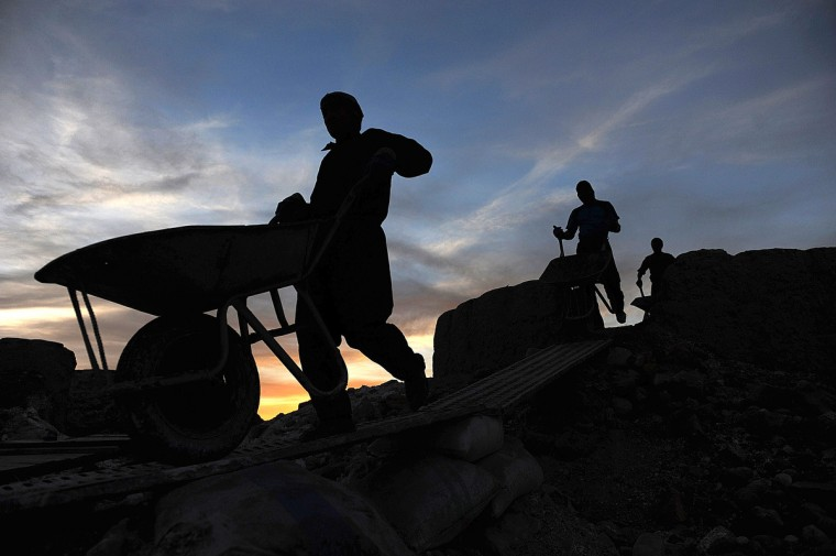 Afghan laborers work at a chalk factory during sunset in Mazar-i-shari. Afghanistan remains an extremely poor country where one in three people live in poverty. (Farshad Usyan/Getty Images)
