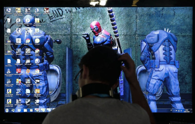 A participant of the technological event Campus Party Brazil, gestures in front of a screen. (Miguel Schincariol/Getty Images)
