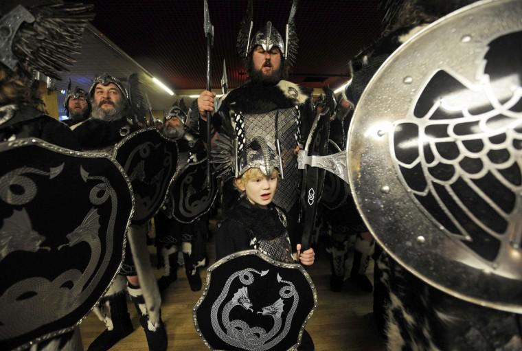 Participants dressed as Vikings prepare to participate in the annual Up Helly Aa festival in Lerwick, Shetland Islands, on January 28, 2014. Up Helly Aa celebrates the influence of the Scandinavian Vikings in the Shetland Islands and culminates with up to 1,000 'guizers' (men in costume) throwing flaming torches into their Viking longboat and setting it alight later in the evening. (Andy Buchanan/Getty Images)