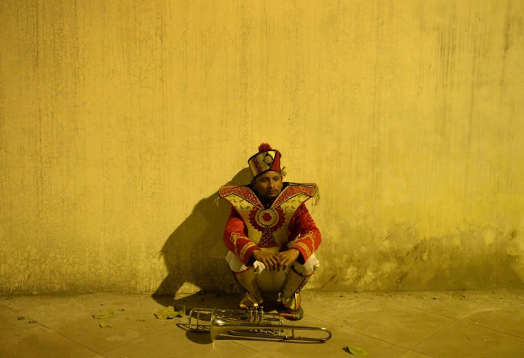 An Indian band member waits at the roadside ahead of the bridal procession in New Delhi on January 28, 2014. South Asian weddings are often lavish affairs, filled with ritual and celebration that continues for several days. (Sajjad Hussain/Getty Images)