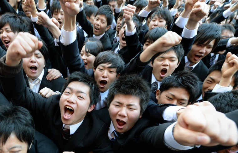 College students shout as they raise their arms at the start of a ceremony to mark the annual job hunt in Tokyo. Some 1,500 students, who will graduate from schools in March 2015, attended the annual ceremony which aims to encourage future graduates to look for employment. (Toru Yamanaka/Getty Images)