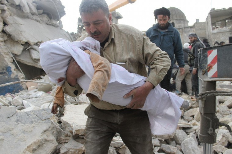 A Syrian man carries the body of a victim out of the rubble of a destroyed building following alleged air raids by government forces on the rebel-controlled part of Aleppo's Maadi residential district on January 29, 2014. The Syrian army is edging its way towards southeastern Aleppo as it battles rebel fighters for control of the northern city, a monitor and a pro-government daily said. (Zein Al-Rifai/Getty Images)