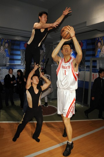 Performers Shougang Yang and Chao Li pose with the wax figure of basketball star Yao Ming during its unveiling at Madame Tussauds on March 18, 2009 in New York City. ( Bryan Bedder/Getty Images)