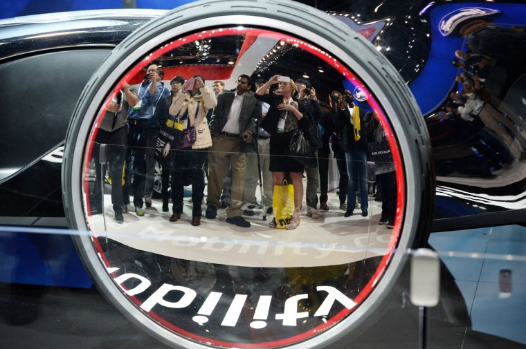 Attendees are reflected in the wheel of the Toyota FV2 future mobility concept car at the 2014 International CES in Las Vegas, Nevada. (Robyn Beck/Getty Images)
