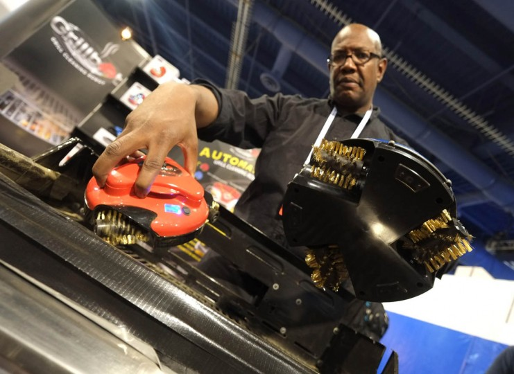 Shawn Dickerson of Grillbot LLC shows grill cleaner robots during the 2014 International CES at the Las Vegas Convention Center in Las Vegas, Nevada. CES, the world's largest annual consumer technology trade show, runs through January 10 and is expected to feature 3,200 exhibitors showing off their latest products and services to about 150,000 attendees. (Joe Klamar/Getty Images)