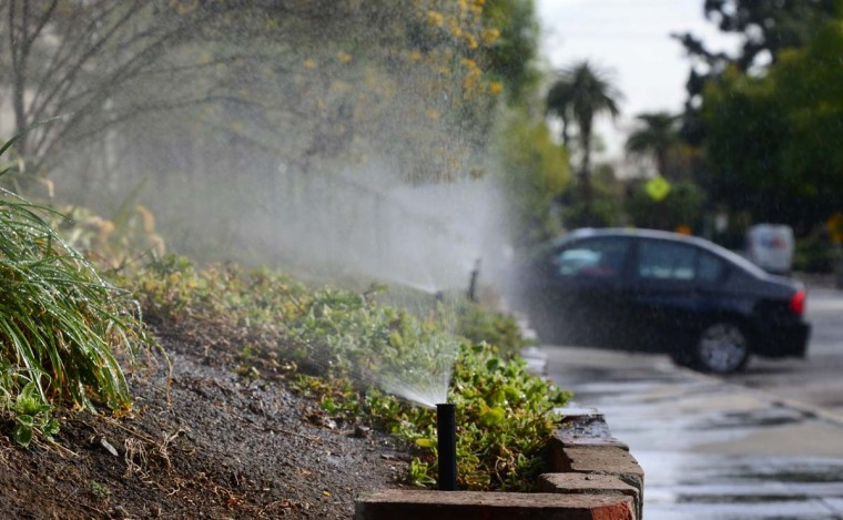 A vehicle enters a driveway at the end of a row of sprinklers watering plants and foliage in front of an apartment complex in South Pasadena, California. (Frederic J. Brown/Getty Images)