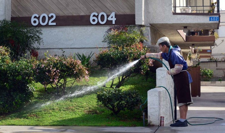 A gardener waters plants and foliage in front of an apartment complex in Monterey Park, California. (Frederic J. Brown/Getty Images)