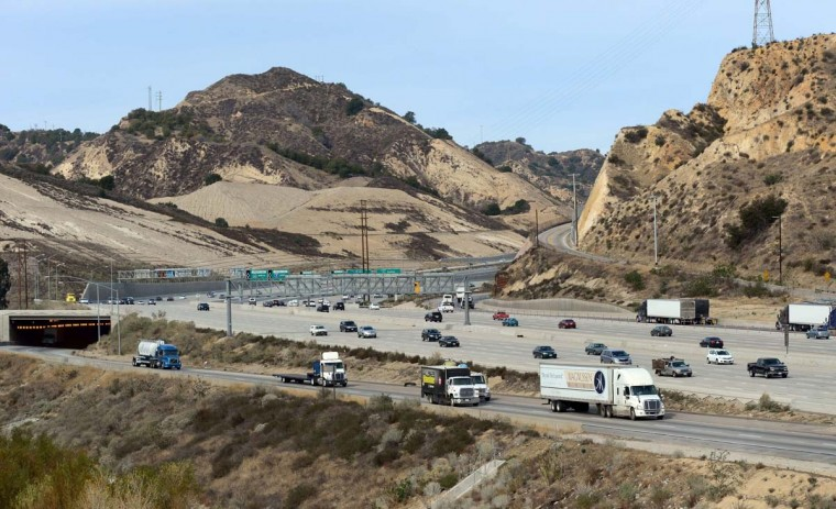 Container trucks and other vehicles pass dry and barren hillsides making their way in and out of southern California. California is suffering its third dry winter in a row. (Frederic J. Brown/Getty Images)