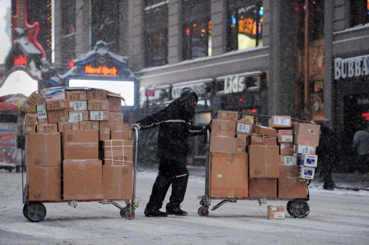 A FedEx delivery man crosses Seventh Avenue in New York's Times Square as snow falls during the rush hour January 21, 2014. (Stan H/Getty Images)
