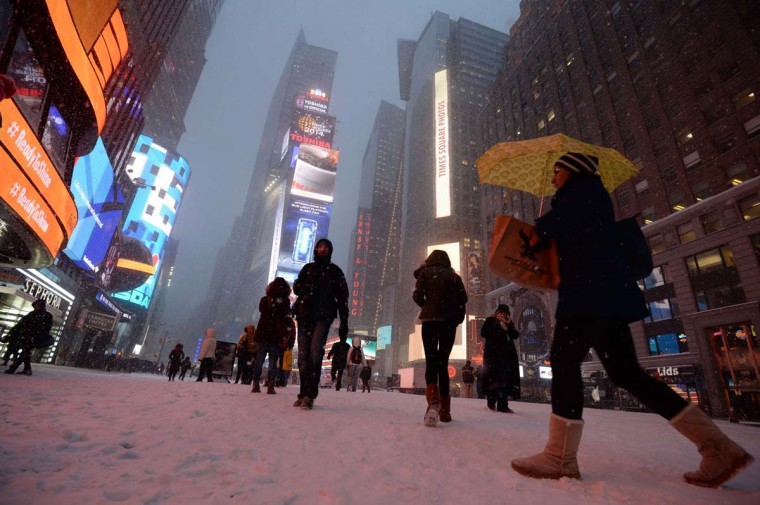 People walk in New York's Times Square as snow falls during the rush hour January 21, 2014. In New York, a storm alert was issued for noon (1700 GMT) Tuesday to 6:00 am (1100 GMT) Wednesday with as much as a foot (30 centimeters) forecast for the metropolitan region. (Stan Honda/Getty Images)