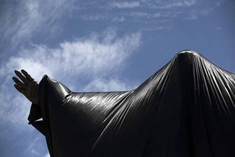 A statue of former South African president Nelson Mandela is covered before being unveiled at the Union Buildings on December 16, 2013 in Pretoria, South Africa. South African president Jacob Zuma unveiled a 9 meter bronze statue of former South African president Nelson Mandela as part of the Day of Reconciliation celebrations. (Photo by Oli Scarff/Getty Images)