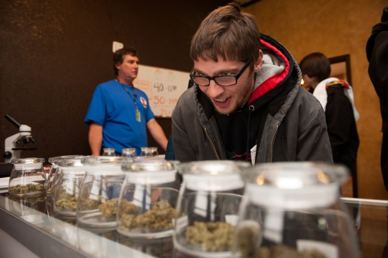 Tyler Williams of Blanchester, Ohio, selects marijuana strains to purchase at the 3-D Denver Discrete Dispensary on Jan. 1, 2014 in Denver, Colo. (Theo Stroomer/Getty Images)