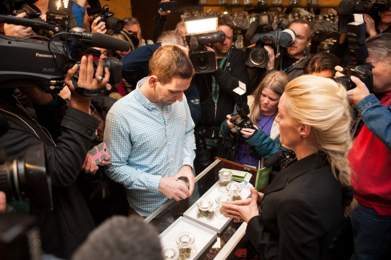 Sean Azzariti, a veteran of the Iraq war, prepares to make the first legal recreational marijuana purchase in Colorado from advocate Betty Aldworth at the 3-D Denver Discrete Dispensary on Jan. 1, 2014 in Denver, Colo. (Theo Stroomer/Getty Images)