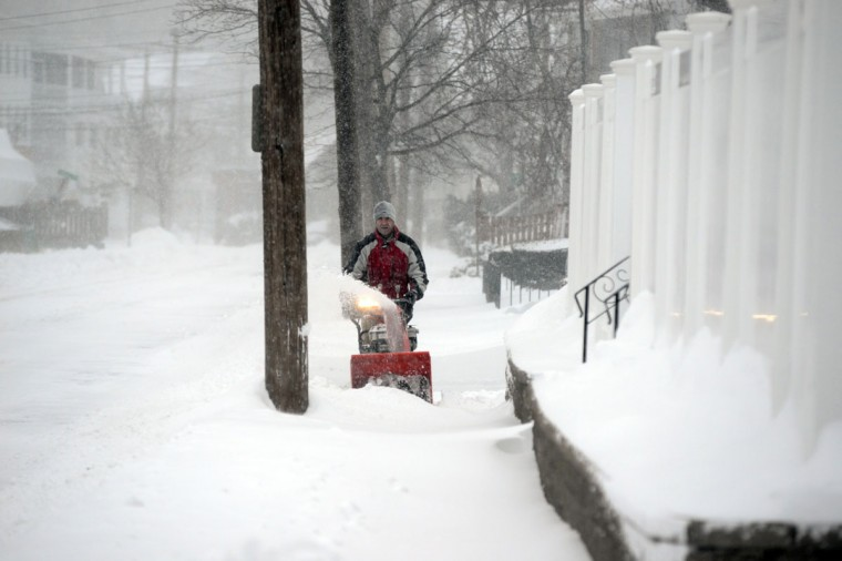 A man snowblows on Shirley Street after an overnight storm January 3, 2014 in Winthrop, Massachusetts. (Photo by Darren McCollester/Getty Images)