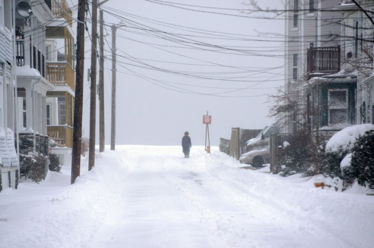 A woman walks down snowy Forrest Street after an overnight storm January 3, 2014 in Winthrop, Massachusetts. (Photo by Darren McCollester/Getty Images)