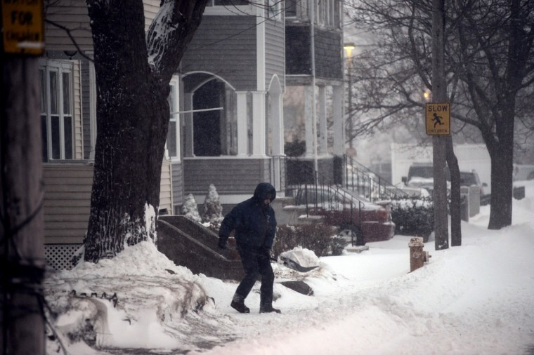 A man shovels snow as the dig out begins on Ocean Avenue on January 3, 2014 in Winthrop, Massachusetts. (Photo by Darren McCollester/Getty Images)
