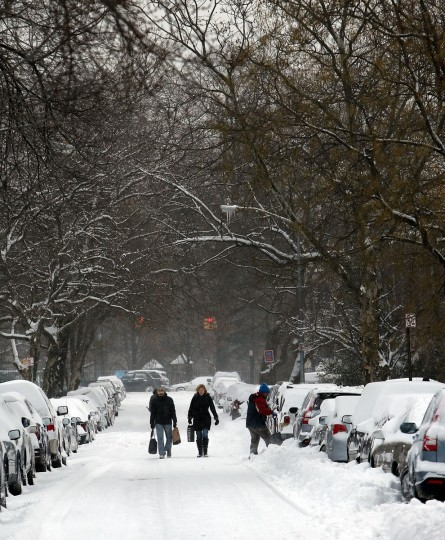 People walk down a snow-covered street in Brooklyn following a storm that left up to 8 inches of snow on January 3, 2014 in New York. (Photo by Spencer Platt/Getty Images)