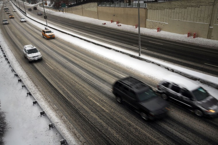 Cars cautiously move down a snow-covered highway in Brooklyn following a snow storm that left up to 8 inches of snow on January 3, 2014. (Photo by Spencer Platt/Getty Images)