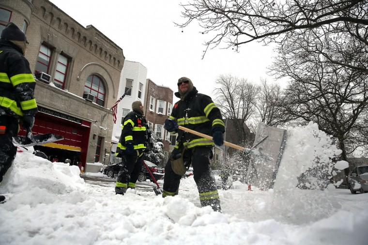 New York City Firefighters dig out of their firehouse in Brooklyn following a storm that left up to 8 inches of snow on January 3, 2014. (Photo by Spencer Platt/Getty Images)