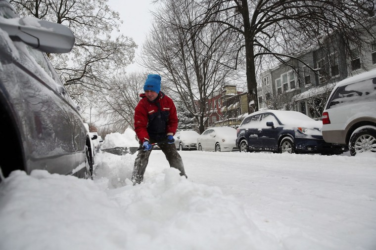 A man digs his car out in Brooklyn following a storm that left up to 8 inches of snow on January 3, 2014. (Photo by Spencer Platt/Getty Images)
