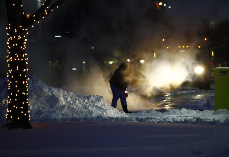 A woman navigates around several inches of snow and steam in Detroit. (Photo by Joshua Lott/Getty Images)