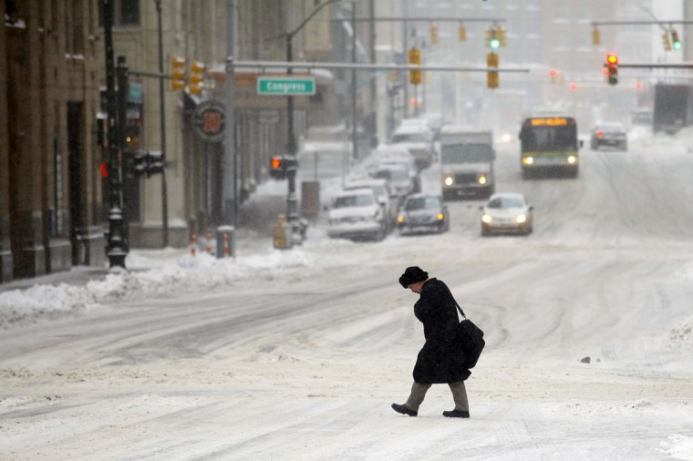 A man navigates through several inches of snow in Detroit as the area deals with record-breaking freezing weather. Michigan and most of the Midwest received its first major snow storm of 2014 last week and subzero temperatures are expected most of this week with wind-chill driving temperatures down to 50-70 degrees below zero. (Photo by Joshua Lott/Getty Images)