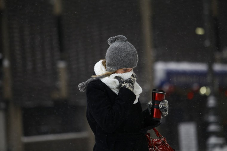 A woman covers her face from the cold as Detroit deals with record-breaking freezing weather. Michigan and most of the Midwest received its first major snow storm of 2014 last week and subzero temperatures are expected most of this week with wind-chill driving temperatures down to 50-70 degrees below zero. (Photo by Joshua Lott/Getty Images)