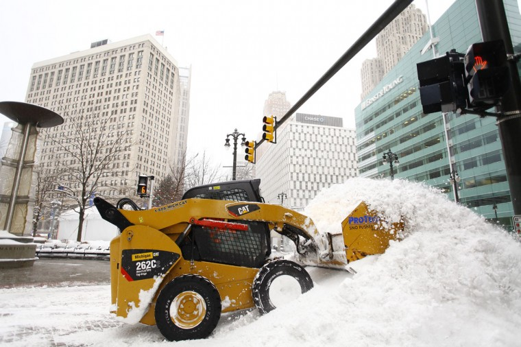 A worker uses a tractor to remove snow along Woodward Avenue as Detroit deals with record-breaking freezing weather. (Photo by Joshua Lott/Getty Images)