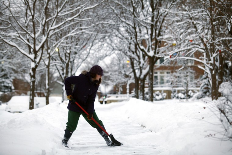 Carly Strachan shovels several inches of snow from her sidewalk in Detroit. (Photo by Joshua Lott/Getty Images)