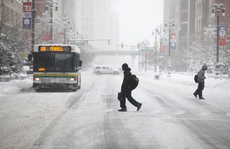 Pedestrians cross Woodward Avenue in Detroit as it snows. (Photo by Joshua Lott/Getty Images)