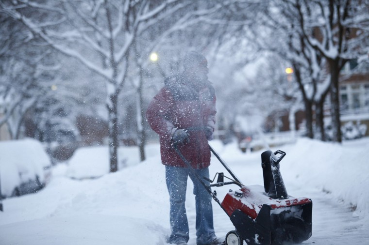 Larry Thomas snow blows several inches from a sidewalk in Detroit. (Photo by Joshua Lott/Getty Images)