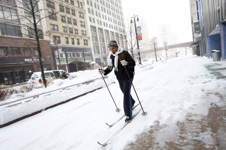 Alison Mueller skies to work through several inches of snow along Woodward Avenue in Detroit. (Photo by Joshua Lott/Getty Images)