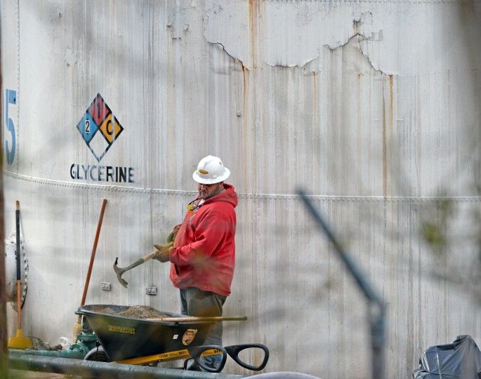 "An unidentified worker at Freedom Industries shovels NAPA premium oil absorbent on January 10, 2014 in Charleston, West Virginia. West Virginia American Water determined Thursday MCHM chemical had ""overwhelmed"" the plant's capacity to keep it out of the water from a spill at Freedom Industries in Charleston. An unknown amount of the hazardous chemical contaminated the public water system for potentially 300,000 people in West Virginia. (Tom Hindman/Getty Images)"