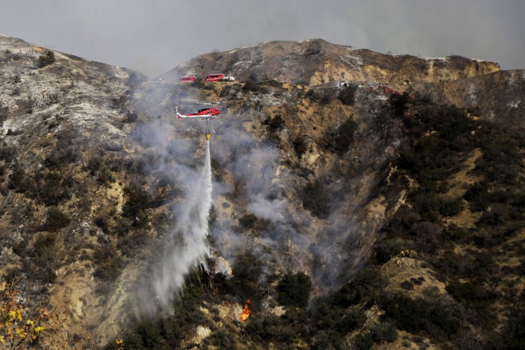 Helicopters work to control wildfires as they burn through the hillsides on January 16, 2014 in Azusa, California. Authorities have stated that three people have been charged with recklessly lighting a fire as the blaze known as the Colby Fire has now destroyed 1,700 acres of land and several homes around Glendora and Azusa in the San Gabriel Valley, prompting officials to order evacuations for houses near the fire. (Dan R. Krauss/Getty Images)