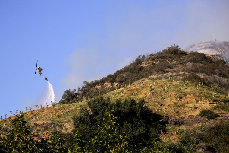 A helicopter works to control wildfires as they burn through hillsides on January 16, 2014 in Azusa, California. Authorities have stated that three people have been charged with recklessly lighting a fire as the blaze known as the Colby Fire has now destroyed 1,700 acres of land and several homes around Glendora and Azusa in the San Gabriel Valley, prompting officials to order evacuations for houses near the fire. (Dan R. Krauss/Getty Images)